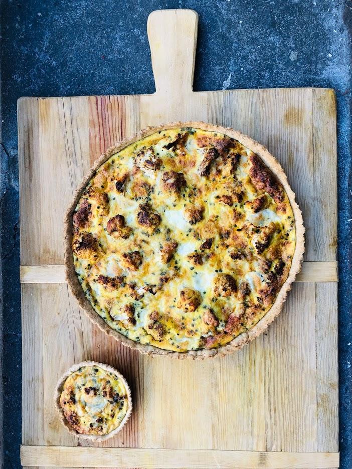 Geroosterde bloemkool quiche met twee soorten kaas en een zelfgemaakte bodem van spelt meel. Een heerlijke vegetarische quiche of hartige taart die ideaal is als avondeten of uitgebreide lunch. Ook heel goed koud te eten.