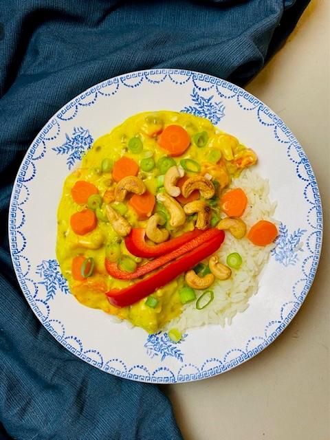 Een heerlijke zelfgemaakte romige vegetarische kokos kerriesaus vol met verse groenten zoals romanesco of bloemkool, wortel en paprika.